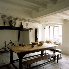 showing table, benches, fireplace, window and cooking implements; the room has been restored to give an impression of a 17th century kitchen.