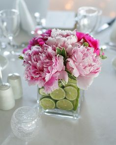 Vase filled with flowers and limes - love these ideas for combining flowers and fruit as centerpieces