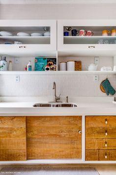 Cozinha branca com azulejos que imitam tijolinho branco, armários com vidro e madeira de demolição.