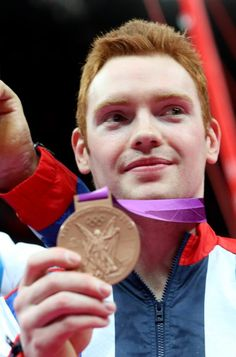 : Bronze medalist Daniel Purvis of Great Britain shows off his bronze medal in the Artistic Gymnastics Men's Team final on Day 3 of the London 2012 Olympic Games at North Greenwich Arena on July 30, 2012 in London, England