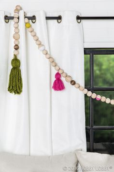 "Add an unexpected element to your space with a DIY beaded garland. 1) Drill a hole through 1 ½"" and 2"" wood spheres to create beads. 2) Paint and stain beads as desired. 3) Once dry, string beads onto suede cording. TIP: Add handmade tassels throughout the garland to achieve a fun and funky look!"