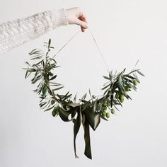 適当な長さのロープにオリーブの枝をワイヤーでくくりつけていき、中央にリボンを結びます。ロープの両端に麻ヒモを結びつけ壁にかけます。ロープがたゆみ半月形のスワッグに。