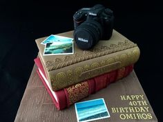 this lovely lady wanted to treat her husband with a cake about his favorite hobbies. Photography and books. So we created a cake of his favorite books, Nikkon camera and some of his own snapshots. Books are chocolate layer cakes, camera is. Lawyer Cake, Library Cake, Camera Cakes, Cake Land, Dad Cake, Create A Cake, Retirement Cakes, Book Cakes, Sculpted Cakes