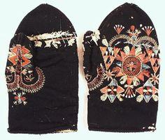 Vantar 1 par, av svart kläde (ull). Innersida av pälsskinn. Tumme och ovansida broderad i brunrött, blått och gult. Sprund på insidan vid fingrarnas plats.