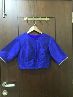 Blue cotton silk closed neck blouse with gold bead pipping and hand work Zardosi work on back. Can be customised to any colour ₹2300/- To book mail at drapemegold@gmail.com Whatsapp : 9892009060