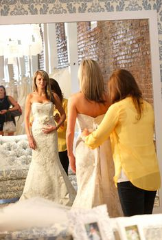 Bride tries on Modern Trousseau's Autumn lace gown at the Nashville flagship showroom.    Photo courtesy of Gregory Byerline.