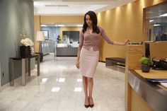 Meghan Markle (Rachel Zane) wears a pink cardigan with a form-fitting pencil skirt