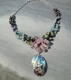 Paua shell with spiral stitched neck band. An original design by Jay Rossi of the Beading Divas.