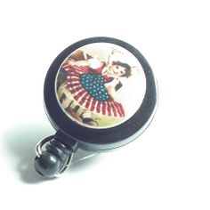 This id badge reel displays a girl in a flag dress on an ivory metal button that is on a black retractable badge reel. A magnet on the back of the reel attaches to your collar, pocket, neckline or whe