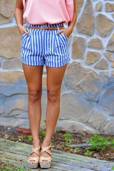pink shirt, striped blue and white shorts and beige sandal heels