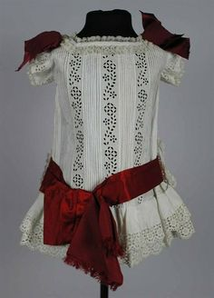 1880 cotton and silk Dutch dress for a child of about three years: dropped waist with double shirred starter strips embroidery. Square, fairly wide neck. Embroidery short sleeves with a wrap on the sleeve cap. Three bows of dark red satin ribbon, and a broad, slightly lighter band with big bow at the back, around the hip. Split center front with concealed closure. On the hips are two loops for wide satin band.