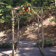 Autumn woodland inspired wedding arbor. Hops and Chinese lanterns bring the color and texture while dahlias, zinnias and delphinium play up the bright orange.