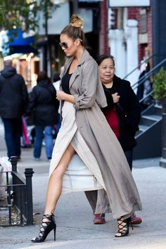 Chrissy Teigen keeps her silhouette loose but put-together in a long coat, cream skirt and lace-up heels.