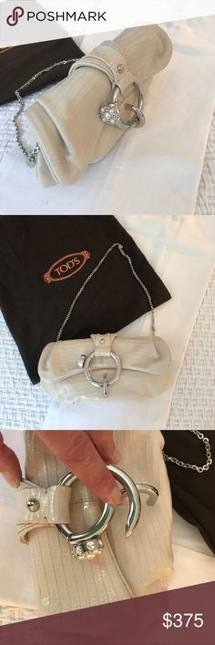 Tod's leather evening bag with jewel clasp This extraordinary off-white leather evening bag from Tod's is most noteworthy for the clasp. The faux-jewel circle opens with a push of your thumb to open and close the bag. You can carry this as a minaudière or wear it over your shoulder. Exceptional used condition. Despite its petite size, it can fit an iPhone 7. My favorite use of this bag is just looking at it on a table. It really is a piece of jewelry. Guaranteed authentic. Comes with…