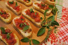 """""""Bruschetta"""" - Um delicioso antepasto italiano feito com a base de pão tipo ciabatta tostado no azeite e coberto com tomates frescos e manjericão. Leia mais..."""