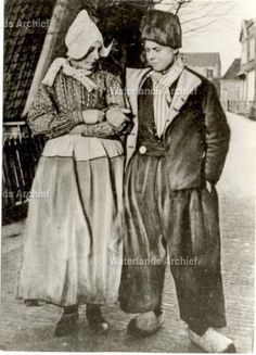 Grietje Kieft (1895-), de latere vrouw van Sijmen Schilder (Doofie; 1893-) in het gezelschap van Cornelis Mooijer (de Schimmel), spieringpakker, vishandelaar 1892-1964. De foto is gemaakt voor de boerderij van Kees Maas aan de dijk tegenover Hotel van Diepen. ca 1915 #NoordHolland #Volendam