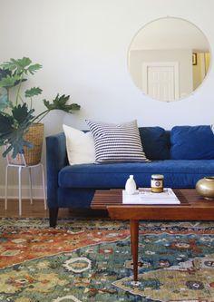 Bright, mid-century modern living room + blue velvet couch + round mirror // Annabode.com