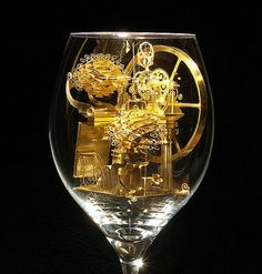 """Szymon Klimek's """"Sponge"""", a solar cell powered miniature that expands and contracts inside a wine glass.  He has created numerous pieces from brass, each delicate beautiful works of art."""