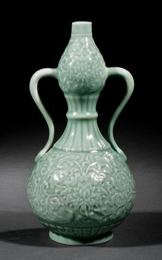 A Chinese Celadon Porcelain Double Gourd Vase, probably Qing Dynasty (1644-1911), upper and lower bulbs relief molded with vining floral sprays and joined together by serpentine handles, neck with radiating petal tips, base with upright petal lappets, base with Yongzheng mark, height 12 in.