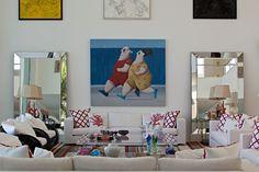 O quadro do artista pl�stico Gustavo Rosa, na parede do living, d� o tom bem-humorado da decora��o. A obra � ladeada por amplos espelhos bisotados que se combinam aos estofados de cores claras e ao tapete listrado. Para dar um ar mais praiano � decora��o da Casa Tabatinga, a arquiteta Selma Tammaro escolheu almofadas com estampas de corais e esculturas que remetem ao mar