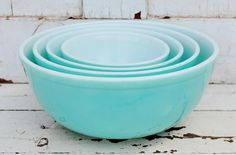 A complete set of four, aqua, nesting, Pyrex mixing bowls. These are from the mid-1950s and are very hard to find. All four bowls are in good condition, with no chips or cracks. The two smaller bowls have significant wear to the painted finish. The insides of the bowls are in very good condition and are shiny white, but do have some scratches from utensils. The largest bowl has a small, slightly discolored spot in the bottom. Specific condition for the exterior of each bowl is listed below…