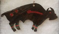 Blackfeet rawhide Buffalo Tipi ornament. The front is painted black with red and green bands on the legs, two red spots to represent wounds and a red arrow which represents the heart line of the animal.