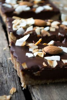 No-Bake Chocolate Tart:1½ cups (190 grams) raw almonds, plus 8 more almonds for garnish ¼ cup (56 grams) coconut oil, melted 1 tablespoon (21 grams) agave nectar 8 ounces (227 grams) dark chocolate, chopped 1 cup coconut milk ¼ cup unsweetened chipped coconut