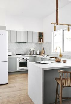 A grey and white palette combined with light timber finishes, gives this kitchen a strong Scandinavian vibe. Photo: Lisa Cohen | Styling: Nat Wheeler