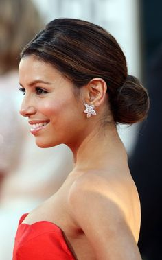 Classic Low Holiday bun on Eva Longoria. In this style, it's super important to smooth all fly away hair to keep it looking super sleek and clean.
