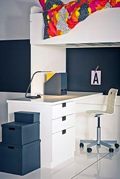 STUVA Schreibtisch in Weiß und Stuhl unter einem Hochbett mit einer bunten Bettdecke