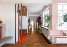 Central to the renovation was making use of a previously enclosed light shaft that pierces through the centre of the apartment. Athens Apartment, Family Apartment, Green Plywood, Plywood Storage, Red Floor, Wooden Dining Tables, Dark Interiors, Apartment Interior Design, Painted Floors