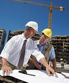 Managers plan out a building. Only place where wearing a hard hat with your suit is proper.