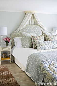 Muted florals: In the master bedroom of a Cape Cod estate, designer Kathryn M. Ireland's Sheer Stripe linen in Blue is draped from a coronet that the designer found at McKinney & Co. in London years ago. The headboard is covered in her Abu linen. Click through for more beautiful designer bedrooms that will have you dreaming of a reno.