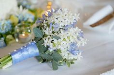 wedding bouquet with pale blue accents | gerbera daisies, lilies and and roses are combined with dark blue ...