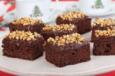 These fabulous brownies are soft and squishy, super-chocolatey and super-nutty. They're packed with walnuts, almonds and pecans, topped with chocolate dulce de leche and sprinkled with more nuts. Perfect with tea! #Brownies #Chocolate #Desserts #Nuts