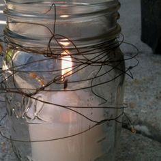 Mason jar candle holder with copper wire and glass beads.  I'm thinking these and some flowers on top of a wood slice for center pieces.