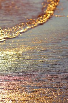 sea sparkle created by the reflection of the sun on the water and wet sand