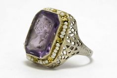 The Susanna Ring. A royal purple carved amethyst will adorn your hand with romance. The carving of an elegant woman is surrounded with a soft halo of natural seed pearls and lacy, floral filigree adorned with 8 yellow gold forget-me-nots. See it in person at our gallery in Santa Barbara, CA, or on the web.