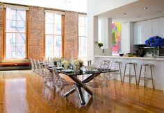 lucite chairs, brick walls, neon art, white glossy kitchen. love