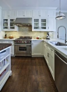 Beautiful white & green contemporary kitchen design with white glass-front shaker cabinets with calcutta marble counter tops, green glass subway tiles backsplash, brushed nickel hardware, white kitchen island with butcher block counter tops and Restoration Hardware Clemson pendants.
