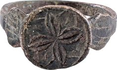 GOOD LARGE BYZANTINE PILGRIM'S RING 7th-10th century AD. Size 9 1/4. Tapered band flared to diamond shapes below the bezel. Circular bezel with cross shaped floweret motif with lineal leaf infill. Well preserved with good patina. While Pilgrims were readily identifiable, they were increasingly less welcome after the introduction of Islam in the 7th century which ultimately contributed to the Crusades. The motif on this ring is likely a dedication to the cross and the sacrifice it…
