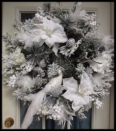 """""""Snow Kissed Christmas"""" Holiday Wreath Elegant handcrafted Christmas wreath filled with gorgeous snow kissed pine, glistening snow flakes, beautiful snow white feathers, and a striking peacock. Decorative holiday wreath measures approx: 30""""."""