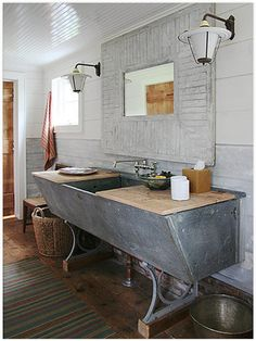 another viable contender for favorite bathroom:  absolute perfect sconces (where are they from?); crazy about the mirror - love the large frame + reasonable size mirror - fanatical about the vanity/wash tub basin; glossy beadboard ceiling; wide-paneled walls; sleek, modern faucet; pine floors; baskets - yes to it all
