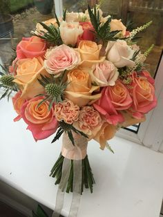 A beautiful bridal bouquet for Suzanne. Peach Avalanche roses, Miss Piggy roses, peach spray roses, apple tea carnations, white astilbe and Eryngium.