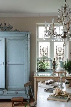 Blue armoire, pretty neutral on the walls, & chandelier- these colors for kitchen
