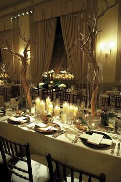 Keeping the venue space natural with the twisting branches and the cluster of white candles. Depending on what you wish to display, color is not always needed.