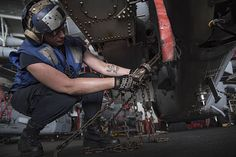 Airman Breanna O'Kelly ties down an MH-60S Sea Hawk helicopter assigned to the Dusty Dogs of Helicopter Sea Combat Squadron (HSC) 7 in the hangar bay of the aircraft carrier USS Dwight D. Eisenhower (CVN 69).