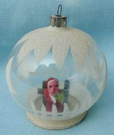 Glass Snow Dome Ornament with Composition German Santa Holding a Tiny Green Feather. It Can Be Hung on a Tree as an Ornament or Stand Alone.