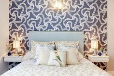 Designer: Nuts & Architects, Paris, France A large wall mural with a striking wallapaper pattern covers a feature wall in this elegant bedroom. The dark blue color in the wall mural complements the lighter colors used in the furniture and soft furnishings.