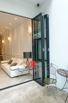 Fabulous Glass Accordion Door With White Wall Then Transparent Chairs Beside Door Plys Glass Nightstand Beside White Sofa Design Idea: Stunning Accordion Doors Design as Home Interior Plans White Sofa Design, Door Design, House Design, Steel Doors And Windows, Accordion Doors, Interior Decorating, Interior Design, Folding Doors, Patio Doors